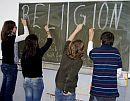 Schüler schreiben RELIGION an eine Tafel